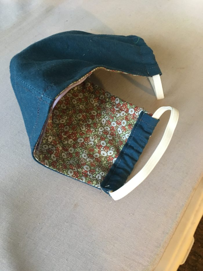 A face mask with elastic ear straps and a floral lining.